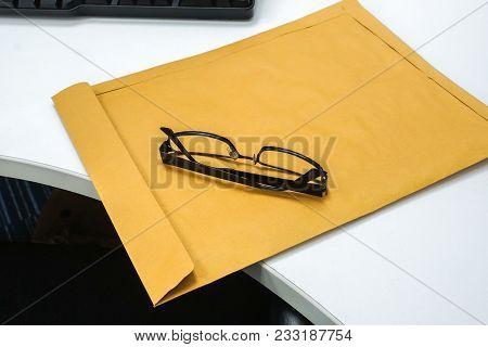 Men Modern Eyeglasses On Brown Confidential Envelope