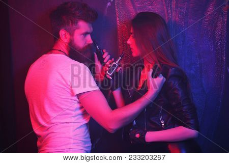 Bearded Man And Girl Posing On Camera And Smoking An Electronic Cigarette. They Release Smoke In A N