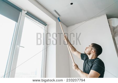 A Man With A Roller In His Hands Paints The Ceiling In The Gray Color Near The Window Of His House.
