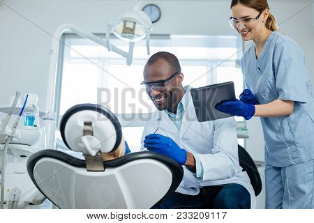 Important Notice. Pleasant Cheerful Nurse Showing Notice On Tablet To An Upbeat Dentist Examining An
