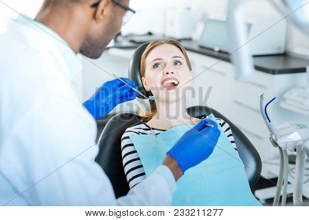 Grateful Patient. Pleasant Young Woman Smiling At Her Male Dentist While Preparing For A Thorough Ex