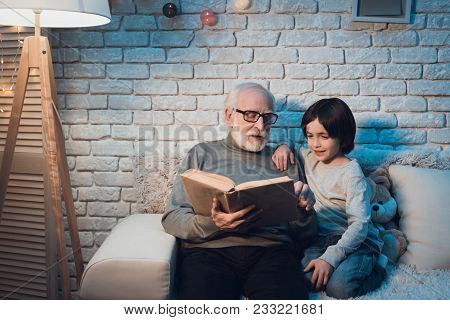 Grandfather and grandson on couch at night at home. Granddad is reading fairy tales book. poster