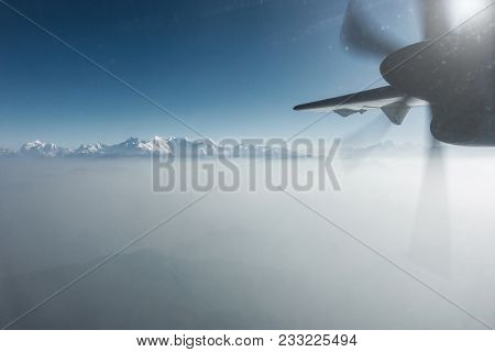 The Himalayas as seen from a propeller plane in Nepal. Layer of clouds beneath the mountain tops.