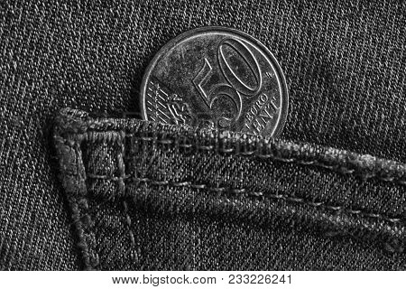 Euro Coin With A Denomination Of Fifty Euro Cents In The Pocket Of Worn Denim Jeans, Monochrome Shot
