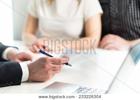 Couple Having Meeting With Legal Advisor, Real Estate Agent, Businessman Or Banker. Lawyer Giving Ad