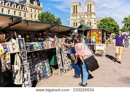Paris, France - June 23, 2017: Vintage Books And Paintings In Open Bookmarket On Embankment Of River