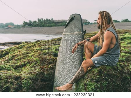 Tanned young surfer with tattoos and dreadlocks with his surfboard, sitting on the green mossy rocks near the ocean in Indonesia, Bali, Canggu, Batu Bolong beach and chilling before surfing. poster