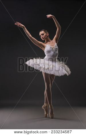 Ballerina In Tutu And Pointe Dancing Gracefully In Dark Room Full-length Shot