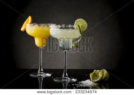 Classic Lime Margarita And Orange Margarita Cocktail Mix In Salt Rimmed Glasses Garnished With Slice