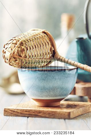 Close up of a ceramic tea cup and wooden tea strainer