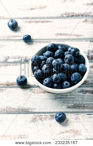 Blueberry, blueberries, fresh berry, berries, bilberry, bilberries served in a small ceramic bowl on white background.