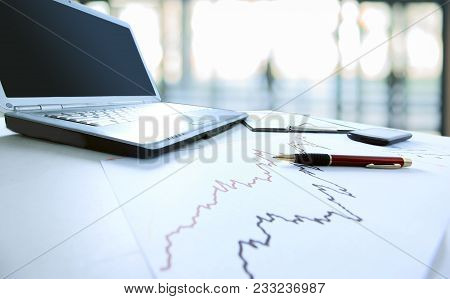 Business Background.a Laptop Computer And Financial Graph On The Desktop .photo With Copy Space
