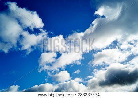 White Clouds In The Sky With Blue Background.