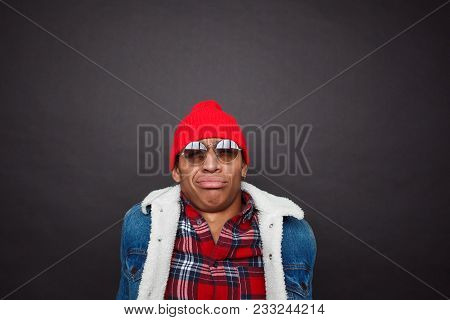 Stylish Black Man In Denim And Red Hat Looking At Through Sunglasses With Emotion Of Disgust.