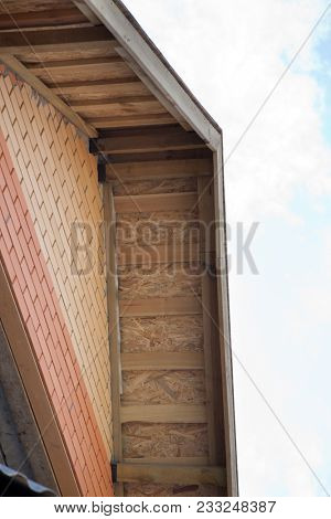 Wall and Roof of the house with exposed wooden beams on the background of blue sky.