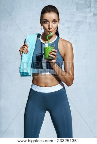 Healthy Lifestyle. Photo Of Latin Fitness Girl With Towel And Glass Of Detox Cocktail On Grey Backgr