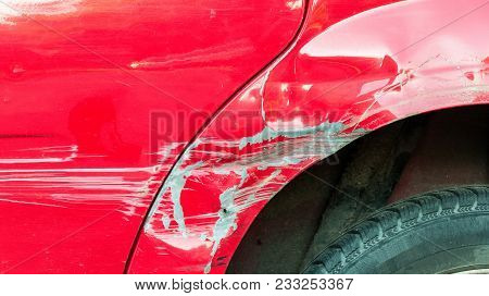 Red Damaged Car In Crash Accident With Scratched Paint And Dented Metal Body