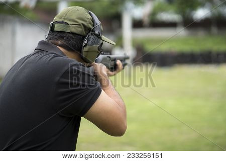 View Of A Man With A Shotgun Reload The Cartridge.