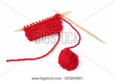 Red Knitting  And Yarn Ball Isolated Over White Background