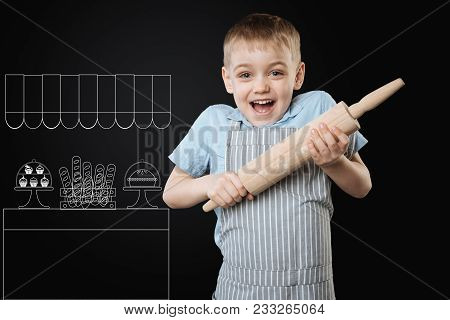 Excited Cook. Enthusiastic Little Boy Feeling Excited While Being In The Kitchen And Holding A Woode