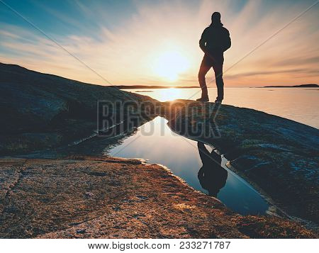Tall Backpacker Watch Clear Sunny Spring Daybreak Over Sea. Hiker With Backpack Stand On Rocky Shore