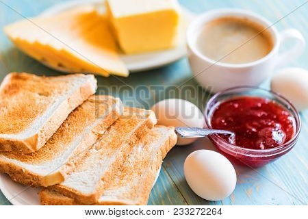 Close Up Table With Delicious Breakfast Coffee, Toasts, Boiled Eggs, Cheese And Strawberry Jam. Cont