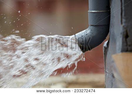 Rain Water Flowing From A Plastic Gutter.