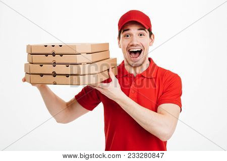 Photo closeup of handsome guy from delivery service in red t-shirt and cap holding stack of pizza boxes isolated over white background