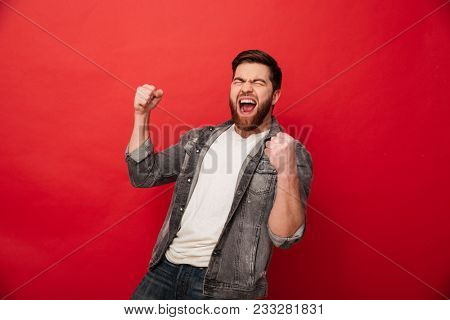 Photo of ecstatic cheerful man 30s in jeans jacket yelling in delight and clenching fists isolated over red background