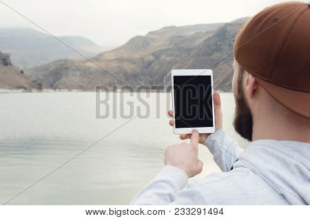 Close-up Of A Hipster In A Brown Cap In The Open Air Holds A White Tablet Pc In His Hands. A Bearded