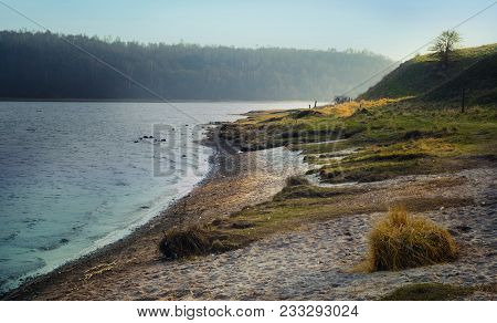Riverbank With Beach And Grass On A Cold Morning In Early Spring, Landscape Of The River Trave Near