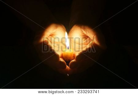Man Hands Holding A Burning Candle In Dark.  Cupped Hands With Burning Candle. Gentle Protection Of