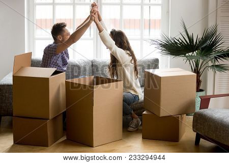 Excited Couple Holding Hands Happy To Move Into New Home, Young Family Celebrate Moving Day Sitting