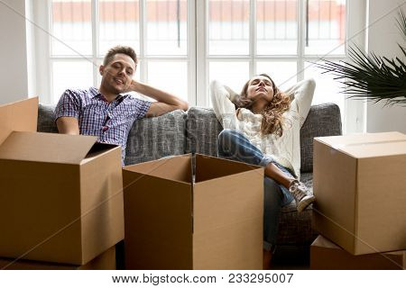 Happy Couple Relaxing On Couch After Moving In New Home, Smiling Young Husband And Wife Homeowners O