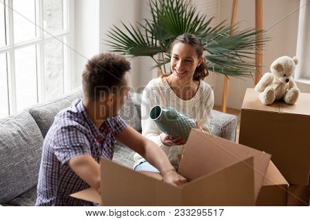 Smiling Couple Packing Cardboard Boxes Together Sitting On Sofa In Living Room Preparing To Relocate