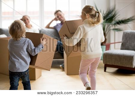 Rear View At Kids Playing With Boxes On Moving Day, Small Brother And Sister Running Holding Belongi