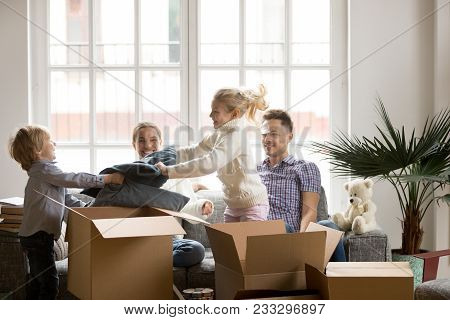 Happy Children Having Fun Pillow Fight While Family Packing Boxes Together On Moving Day, Parents La