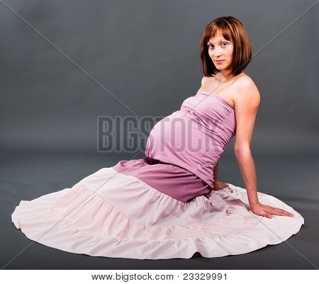 Portrait Of Pregnant Woman On Gray Background