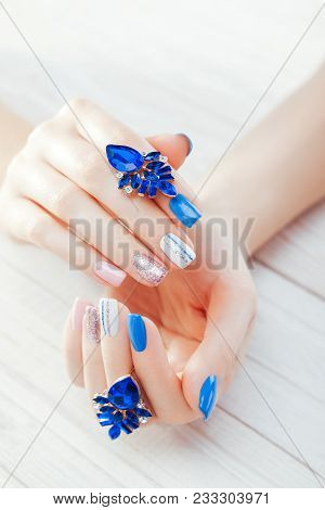 Beautiful Manicure With Earrings. Combination Of Blue, White, Pink Colors And Sparkles. Female Hands