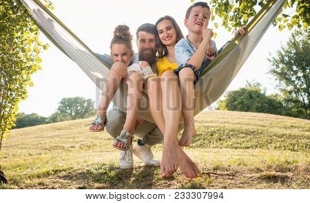 Family portrait with a beautiful mother of two playful children swinging in a hammock while looking at camera next to her husband outdoors in summer
