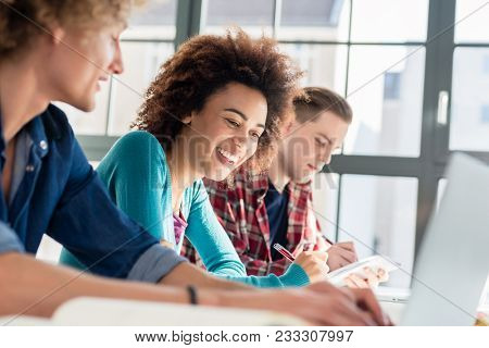 Cheerful young woman writing an assignment while sitting at desk between two classmates during class at college or university