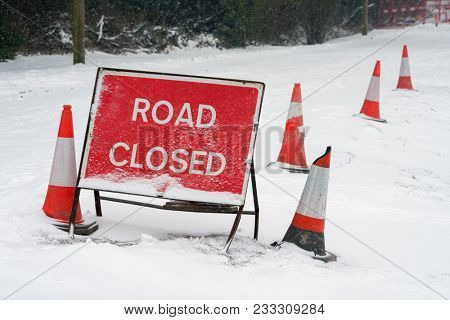 A red Road Closed sign and traffic cones covered in fresh fallen snow on a lane in Hampshire, England. Taken on 2nd March 2018.