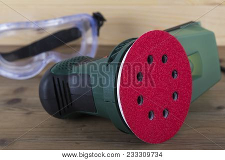 Orbital Power Sander With Red Sanding Disc And Goggles