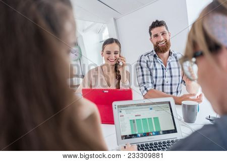 Active female entrepreneur talking on mobile phone, while using a tablet next to her helpful co-worker at a shared desk in a modern collaborative office space