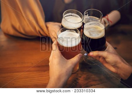 Hands Of People Holding Beer And Cheering In Brewery Pub. People Toasting With Delicious Beer  In Ba