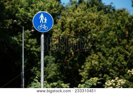 Pedestrian Bicycle Zone In Blue Circle On Background Of Green Trees In Park. City Street Sign Concep