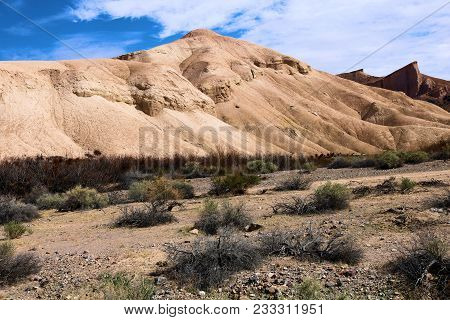 Badlands Landscape With Dried Up Mud Of Sandstone Surrounded By Sage Taken In The Mojave Desert, Ca
