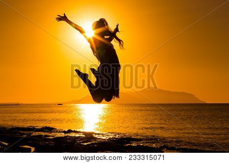 Silhouette Of Happy Girl Jumping Against Sunrise At The Sea
