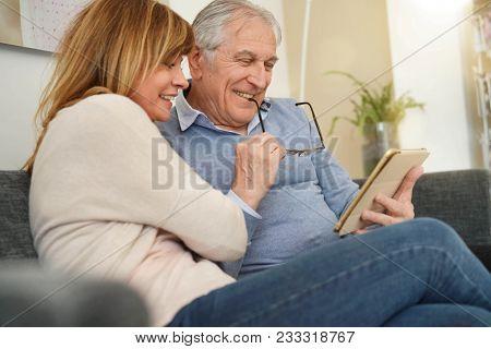 Senior couple in sofa websurfing on digital tablet