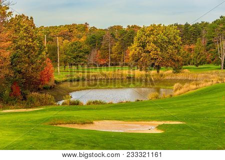A Golf Course Water Trap And Fairways Amid Autumn Colors